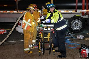 Paramedics attend to patient on a stretcher at the scene. photo by Rick McClure, for The Signal.