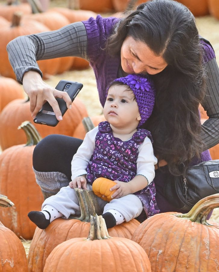 Wendy Jacobo and eight-month-old daughter Vanessa take a photo in the pumpkin patch at the inaugural Harvest Festival held at Gilchrist Farm in Saugus on Saturday. Dan Watson/The Signal