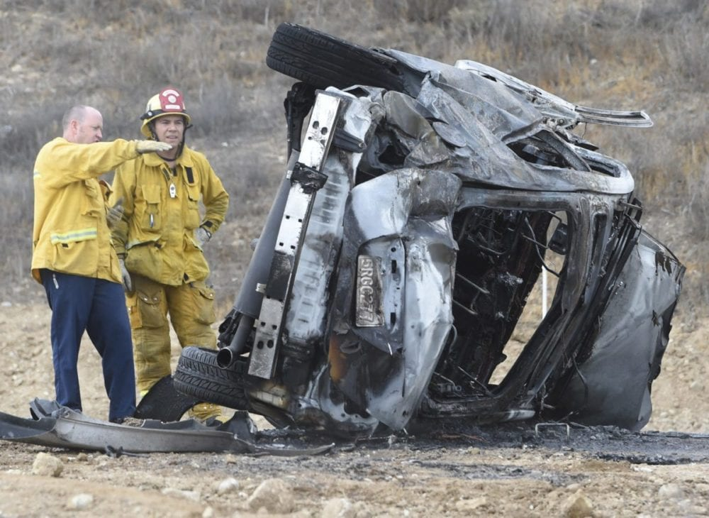 Firefighters inspect a vehicle that rolled down a hill and caught fire the Plum Canyon area on Saturday. Two occupants were transported by ambulance, extent of injuries unknown on Saturday afternoon. Dan Watson/The Signal