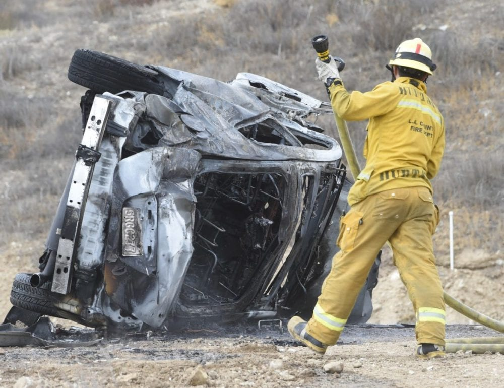 A firefighter moves a hose line into position after vehicle that rolled down a hill and caught fire the Plum Canyon area on Saturday. Two occupants were transported by ambulance, extent of injuries unknown on Saturday afternoon. Dan Watson/The Signal