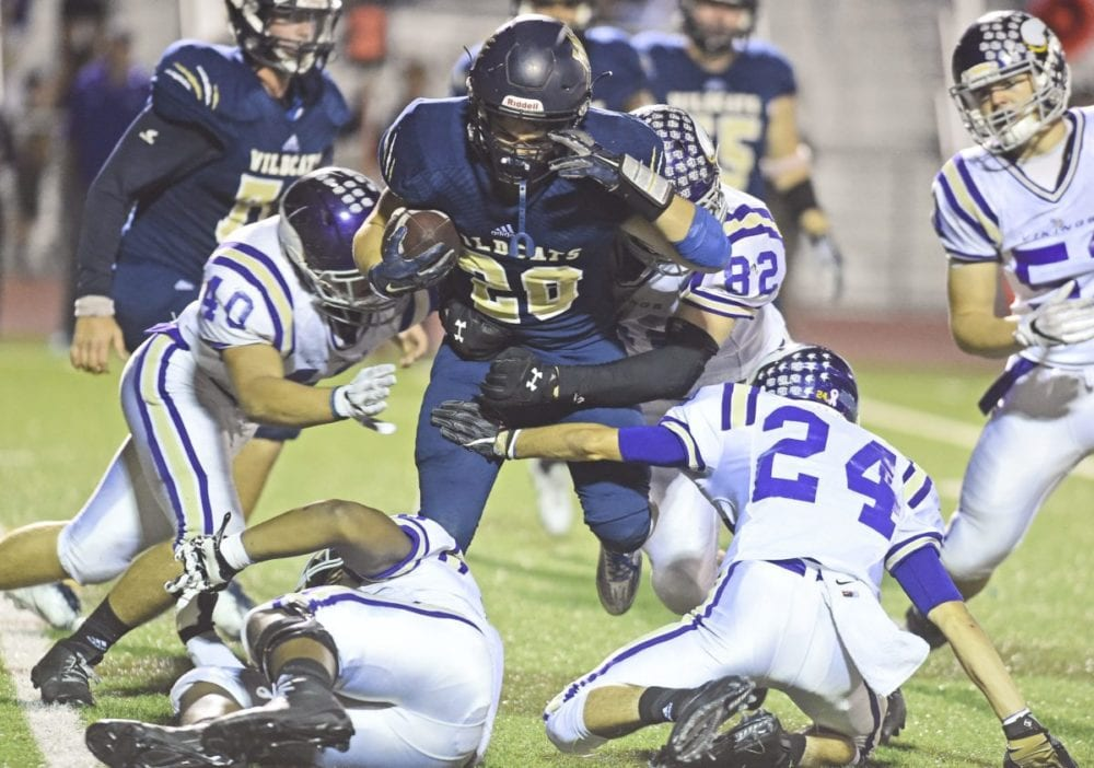 Valencia defenders Reilly Royce (40), Josh DeNeal (82) and Cameron Gearhart (24) bring down West Ranch running back Jake Rice at Valencia on Friday. Dan Watson/The Signal