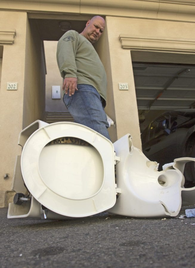Sgt. Jeff Siroonian uses his foot to overturn a piece of broken porcelain from a toilet. Austin Dave/The Signal