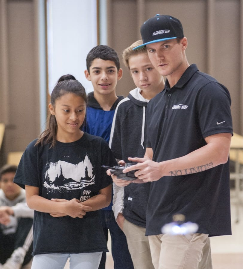 Lizbeth Platas (L), Nicholas Serrano (C) and Kyle Gordon (R), students in Karen Cowell's Engineering Applications class at Castaic Middle School, watch as Ryan Cowell, (wearing hat) Co-Founder of Soaring Sky, demonstrates flying a drone. Tom Cruze/For the Signal