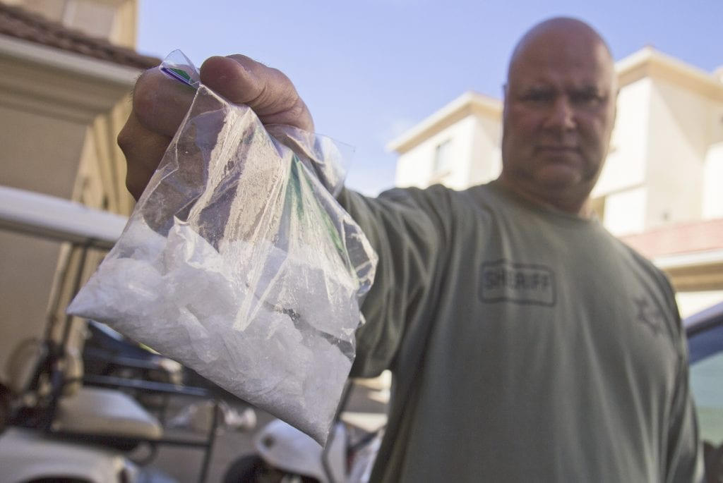 Sheriff's Sgt. Jeff Siroonian holds a bag of crystal methamphetamine nabbed in a drug bust Wednesday. Austin Dave/The Signal
