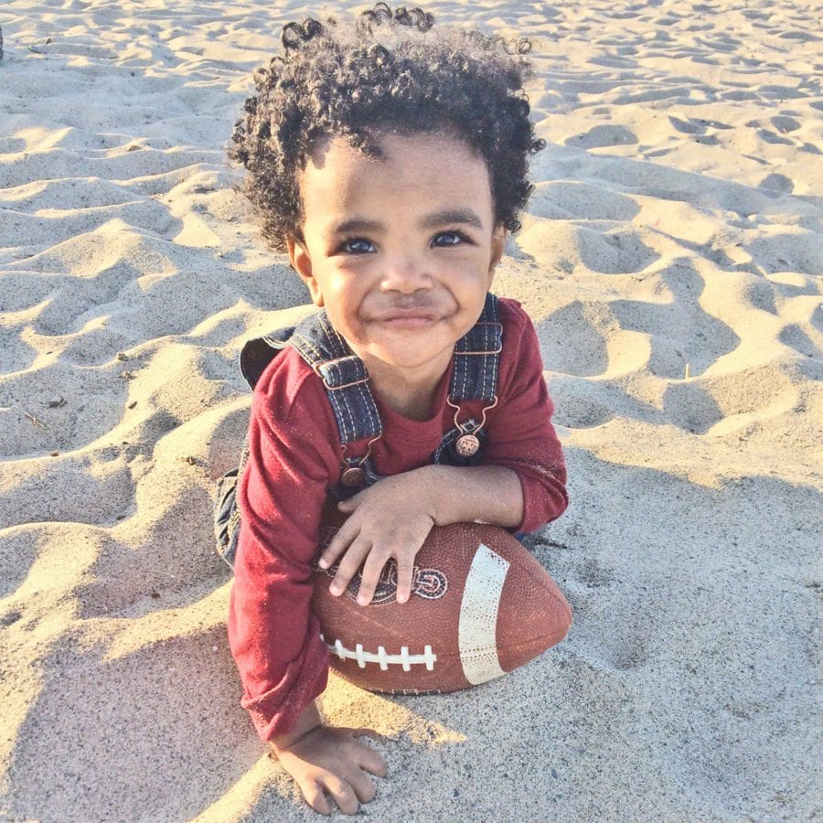 Brown's son, Noah, holds a Golden Valley football at the beach. Courtesy photo.