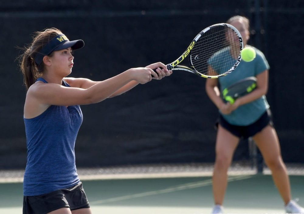 West Ranch High's Emily Andrews hits the ball as partner Audrey Kim plays the back court in their second-round doubles match against Valencia during day one of the Foothill League girls tennis individual tournament at the Paseo Club. Photo by Jayne Kamin-Oncea/For The Signal