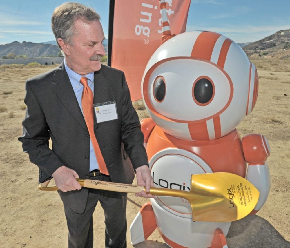 "Dave Styler, President and CEO of Logix Federal Credit Union, left, takes the gold shovel from the company mascot, ""Robix"" in preparation for the official ground breaking ceremony at the location of the the new Logix Headquarters building in Valencia on Wednesday. Dan Watson/The Signal"