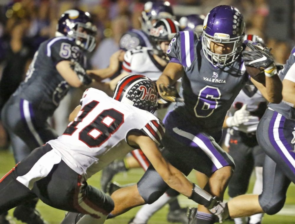 Valencia's Jayvaun Wilson (6) beats a tackle by Hart's AJ Stanley (18) during the teams' Foothill League opener at Valencia on Friday. Katharine Lotze/Signal
