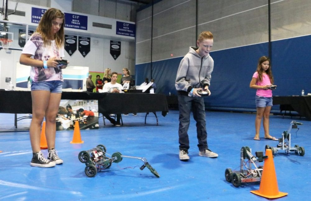 From left to right, Kaitlyn Galvez, 11, Dean Kessler, 11, and Emily Galvez, 8, control robots at the S.T.R.E.A.M Kid's Expo at Saugus High School on Saturday, Oct. 22, 2016. Nikolas Samuels/The Signal