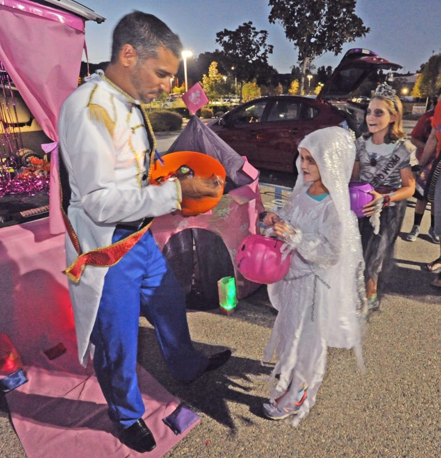 Prince Charming Ray Garcia, left, hands out candy to some of the hundreds of attendees at the 3rd annual Trunk or Treat held at NorthPark (cq) Community Church in Valencia on Friday. Dan Watson/The Signal