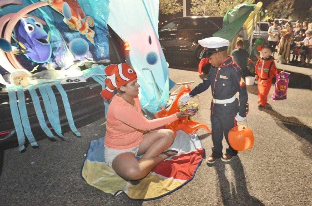 Mary Heitmann, left, hands out candy to Caden Wrighster, 5, in his U.S. Marine costume from the trunk of her SUV with a Finding Dory theme, one of 36 trunks on hand at the 3rd annual Trunk or Treat held at NorthPark (cq) Community Church in Valencia on Friday. Dan Watson/The Signal
