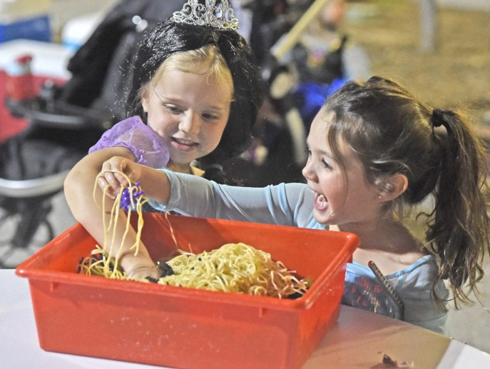 "Cora Bond, left, and Avery Pomeroy react as thye put their hands into a"" tray of worms"" at the 3rd annual Trunk or Treat held at NorthPark (cq) Community Church in Valencia on Friday. Dan Watson/The Signal"