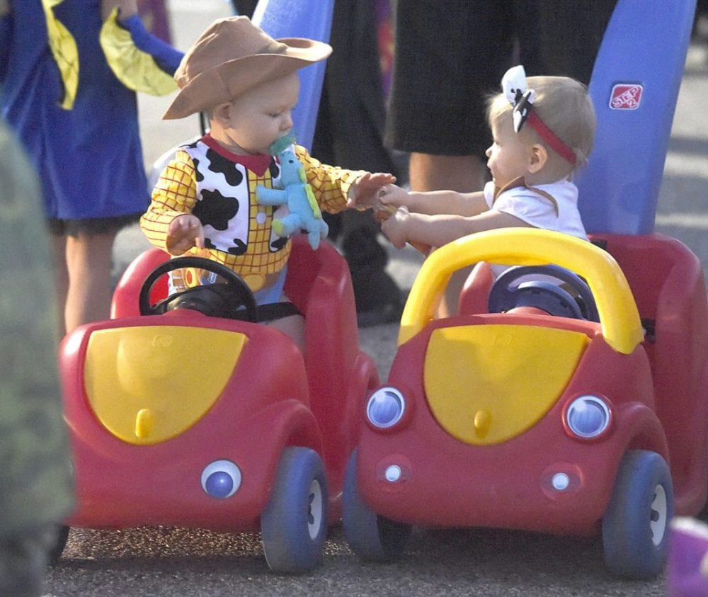 Ten-month-old twins Henry and Claire Axline in the Toy Story costumes ride from trunk to trunk at the 3rd annual Trunk or Treat held at NorthPark (cq) Community Church in Valencia on Friday. Dan Watson/The Signal