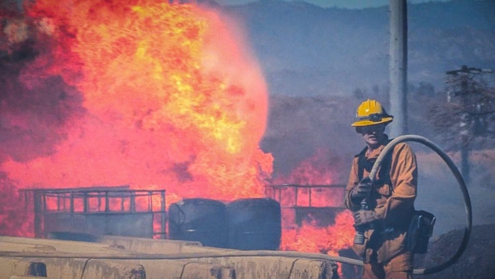 A Los Angeles County firefighter enforces a perimeter around a blaze involving unknown materials in Canyon Country Thursday. Austin Dave/The Signal