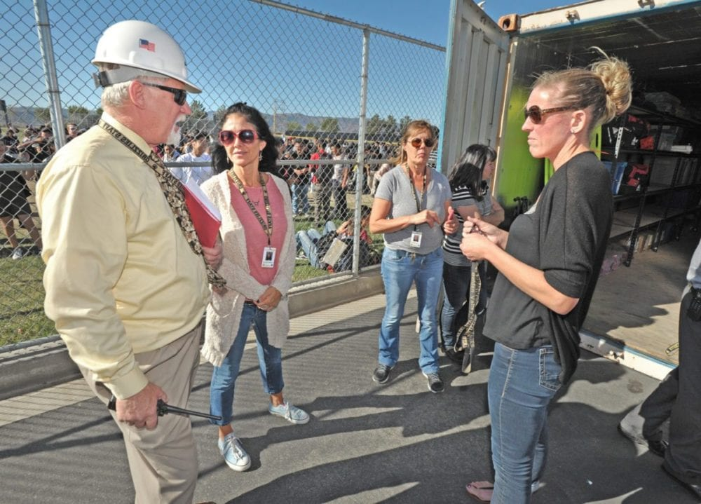 Golden Valley High School Assistant Principal Joel Nelson, left, discusses the emergency provisions on hand in a storage unit during the the Great California ShakeOut drill held at Golden Valley High School on Thursday. Dan Watson/The Signal