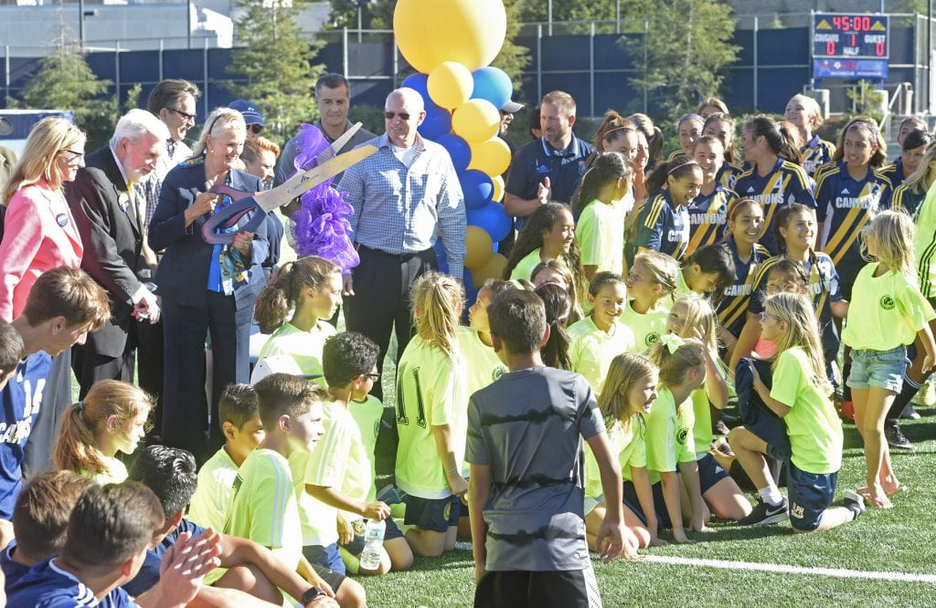 dozens of members of the various soccer teams who will use the field join dignitaries and College of the Canyons President and CEO Dianne Van Hook, center, as she cuts the ribbon during the official ribbon cutting ceremony of the new state-of-the-art COC soccer field at the Valencia campus on Tuesday.  Dan Watson/The Signal
