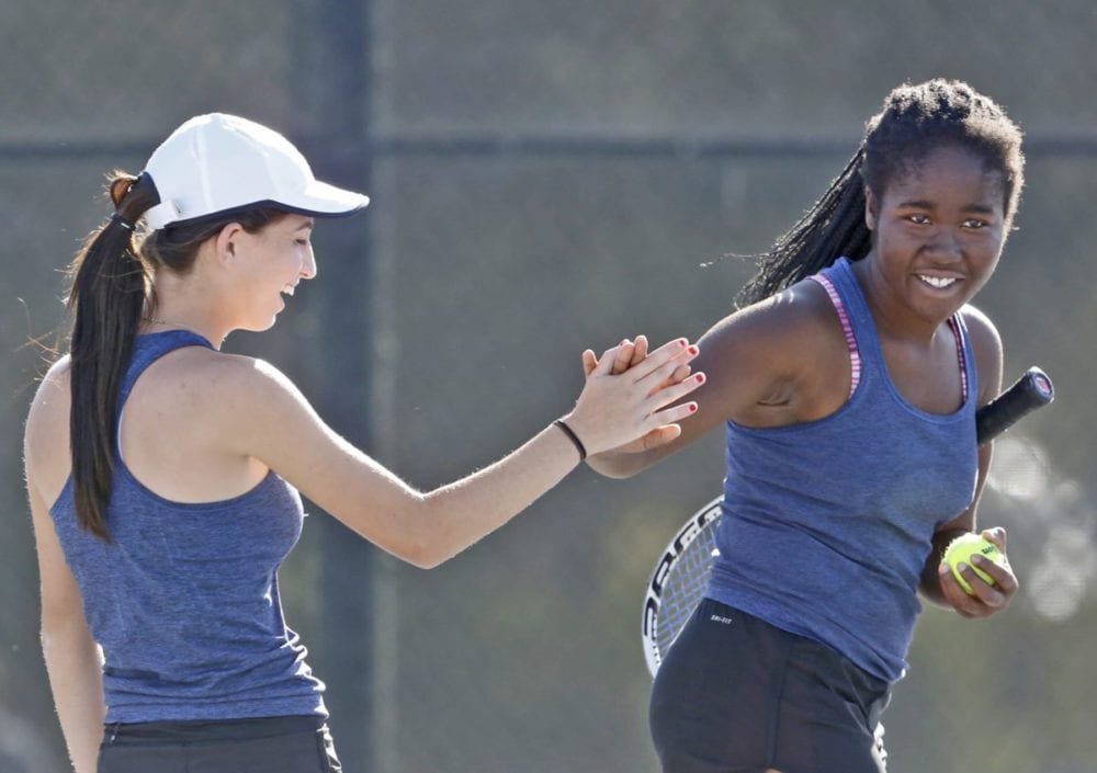 West Ranch second doubles players Cori Raffish, left, and Quinterra Walter-Eze, right, high-five between matches at Valencia on Tuesday. Katharine Lotze/Signal