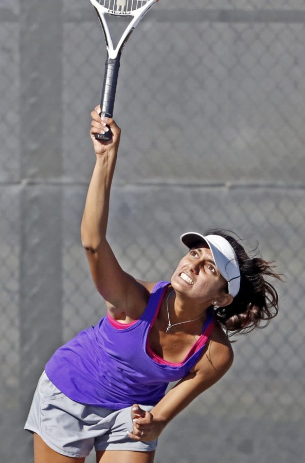 Valencia High's Ashita Tanwar serves the ball to her opponent from West Ranch during a tennis match at Valencia on Tuesday. Katharine Lotze/Signal