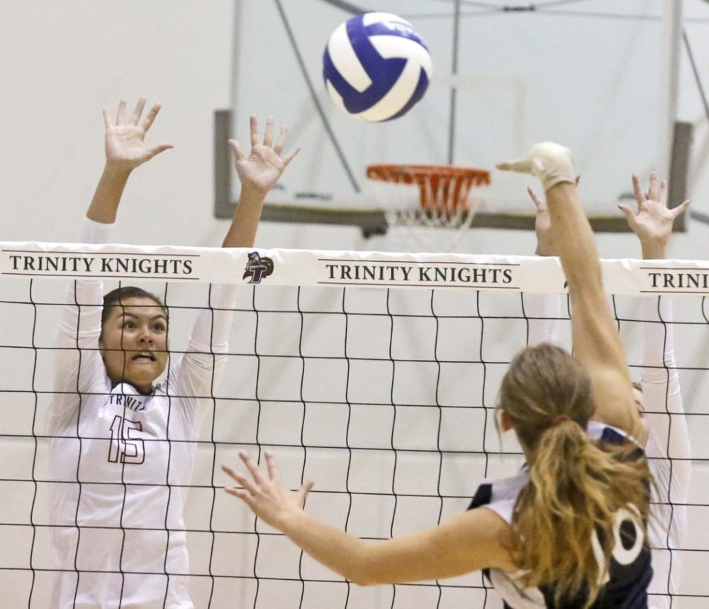 Trinity's Taylor Oshiro (15) jumps to block a hit by Lancaster's Nikole Seher (10) during their volleyball match at the Henry Mayo Health and Fitness Center in Valencia on Monday. Katharine Lotze/Signal