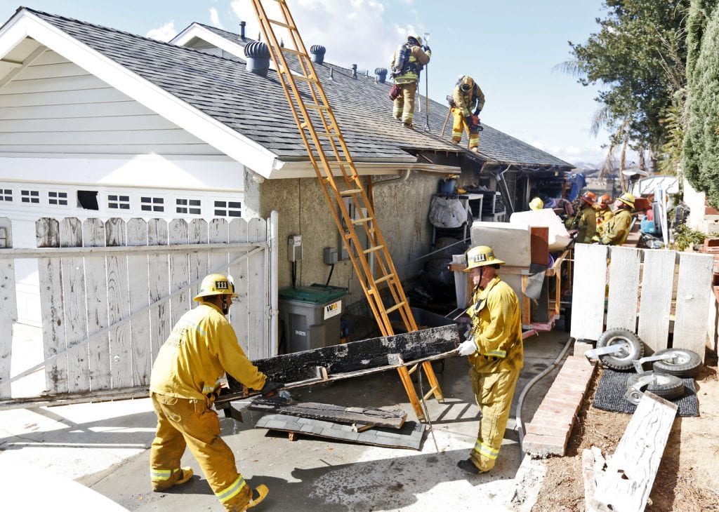 Los Angeles County firefighters carry away a piece of a roof from a home Palmetto Drive in Saugus after a fire broke out in the garage on Monday. Katharine Lotze/Signal