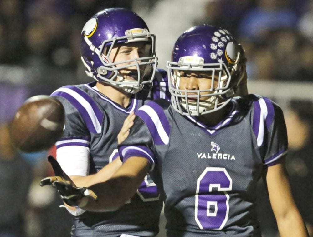 Valencia's Jayvaun Wilson (6) tosses the ball back to the referee as he and teammate Aaron Thomas (15) celebrate Wilson's touchdown for the Vikings in their Foothill League opener against Hart last Friday Katharine Lotze/The Signal