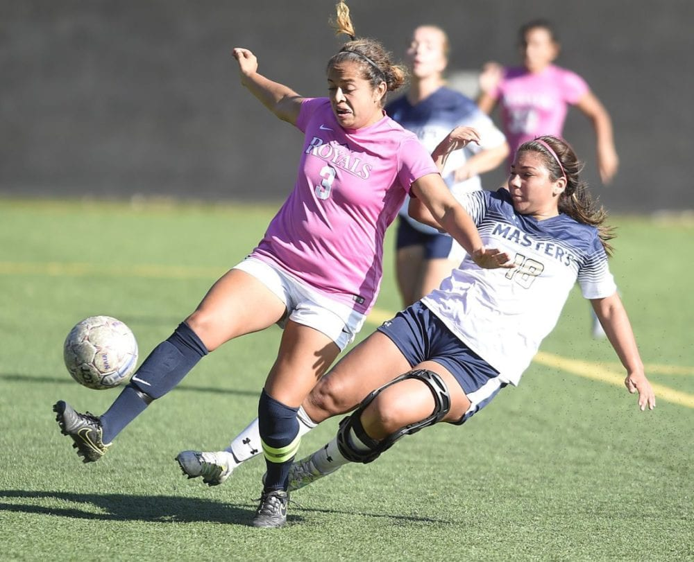 The Master's University forward Sierra Carrasco (18) takes a shot on goal as Hope International's Amanda George (3) defends at TMU on Tuesday. Dan Watson/The Signal