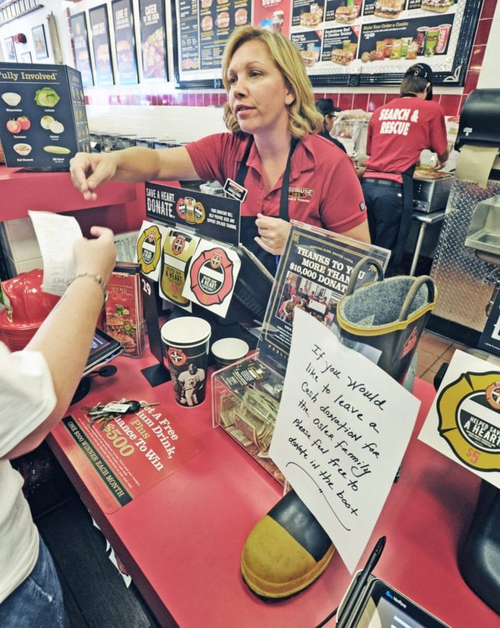 A firefighers boot for donations to the Ryan Osler family stands next to the register as Firehouse Subs owner Jennifer Press serves customers at the Valencia store on Tuesday. 30 % of all sales on Tuesday at the the Valencia and Simi Valley Firehouse Subs will be donated to the Osler family. Dan Watson/The Signal