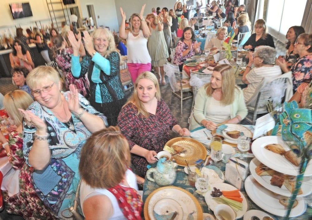 """A conga line of women clap and dance to the song """"Celebration"""" as they weave through the tables to begin the program during the 13th annual Circle of Hope Afternoon Tea event held at Robinson Ranch Golf Course in Santa Clarita on Saturday.  Dan Watson/The Signal"""