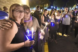 Terri Owen, left, and friend Lia Robin hug as they join hundreds of attendees at a candlelight vigil honoring Sgt. Owen at the Santa Clarita Sheriff's Station in Valencia on Saturday.  Dan Watson/The Signal