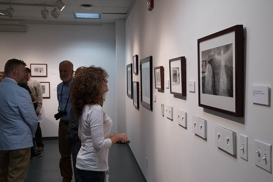 """Individuals look at art pieces from the """"When Man to Man is Wolf"""" exhibit at College of Canyons.  Photo Courtesy of Juan Renteria"""