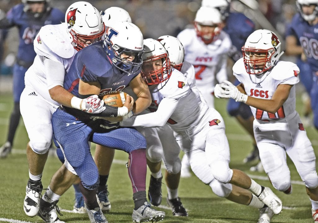 Trinity's Caden Kulp (22) is smothered behind the line of scrimmage by Josiah Park, left, and Aidan Espinosa of SCCS at Canyon High on Saturday. Dan Watson/The Signal