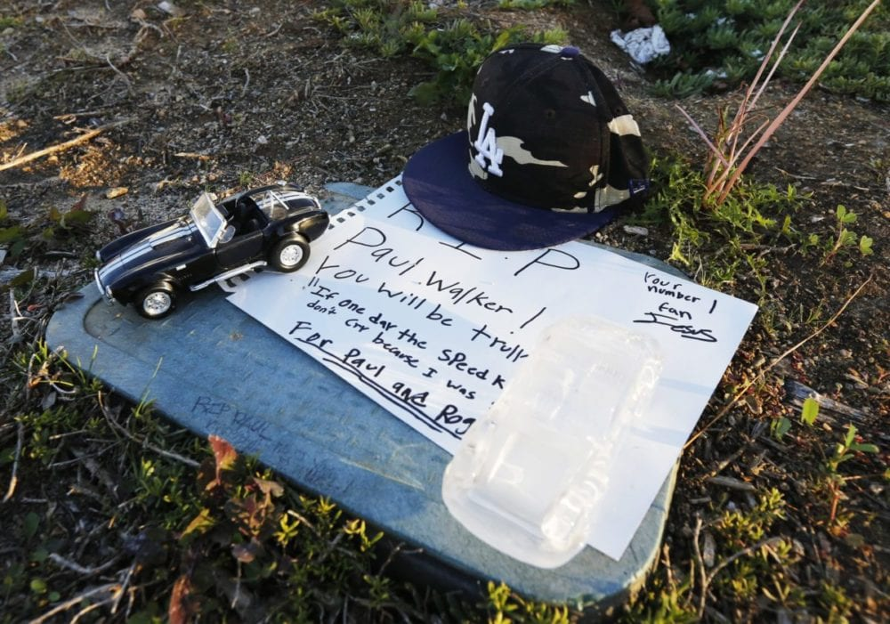 A Los Angeles Dodgers hat, along with two miniature Porche-style cars hold down a written note left by a Paul Walker fan near the site of the fatal car crash that killed the actor and the drive of the vehicle three years ago Wednesday. Katharine Lotze/Signal