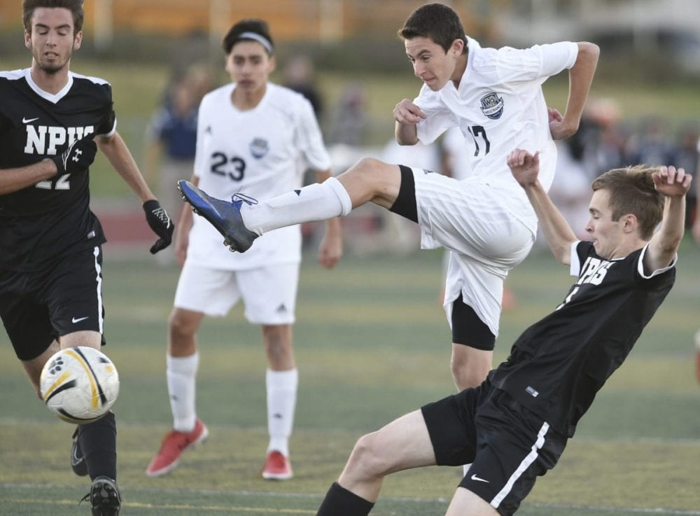 West Ranch's Connor Dresser (17) takes a non-scoring shot on goal agaist Newbury Park defender Jack Hughes (5) in the Second half at West Ranch on Tuesday.  Dan Watson/The Signal