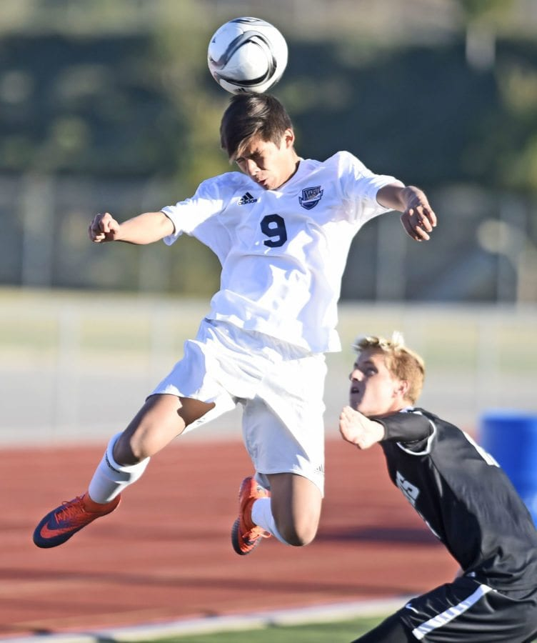 West Ranch's Danny Paredes (9) heads a pass away from  Newbury Park defender Dane Frisel (17) at West Ranch on Tuesday.  Dan Watson/The Signal