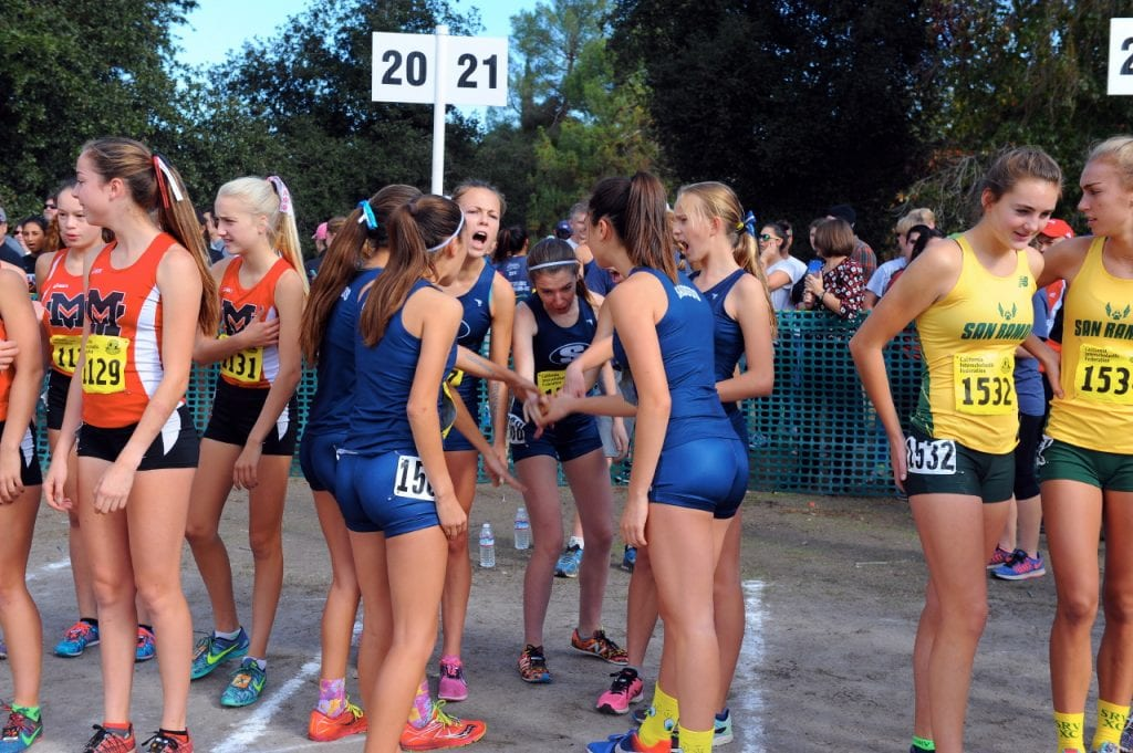 The Saugus girls cross country team huddles before its D2 race on Saturday. Photo by Leonard Coutin/For The Signal