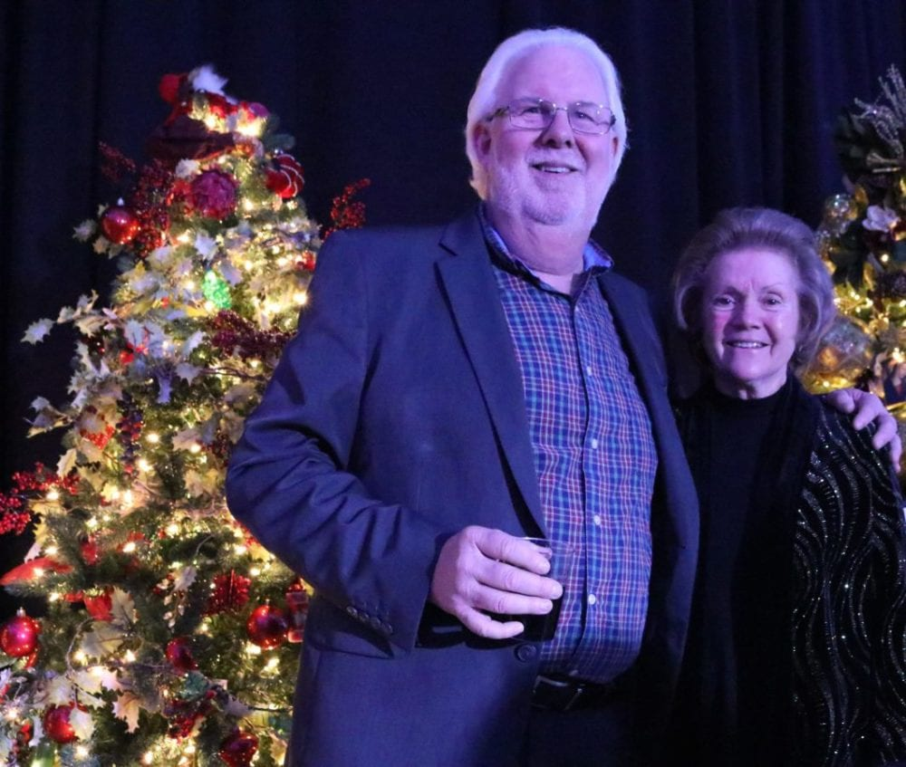 Russ Briley, the Executive Vice President of Community Relations and Audience Development at The Santa Clarita Valley Signal, and Jo Lasick of The Signal, stand in front of their red, wine-themed Christmas tree that won first prize at the Magic of the Lights Gala event at the Santa Clarita Sports Complex on Saturday. Nikolas Samuels/The Signal