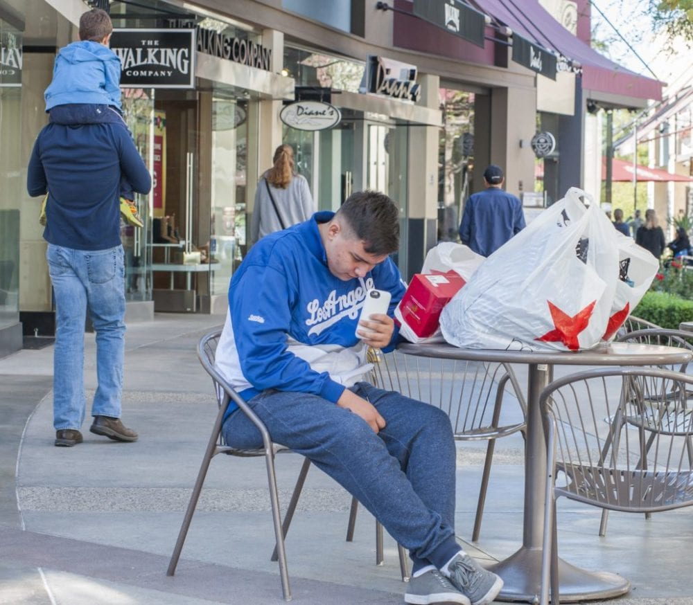 Tony Alvarez watches over purchases as he waits for his mom to complete her shopping at the Westfield Valencia Town Center on Black Friday. Photo Tom Cruze/For the Signal