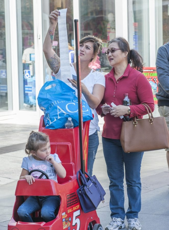 """Stacy Charland (L) checks the receipt with her mother Kim Fowler after making """"a good deal"""" at The Children's Place while shopping at the Westfield Valencia Town Center on Black Friday. In the stroller is daughter Lilly. Photo Tom Cruze/For the Signal"""