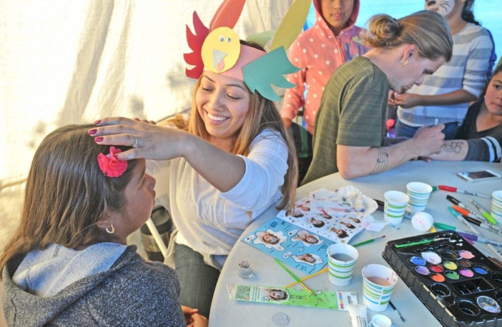 Diana Lemos, center, wears a turkey hat as she paints the faces of children in the craft tent at the 12th Giving Thanksgiving event held in Newhall on Thursday. Dan Watson/The Signal