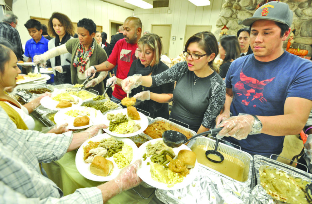 Some of the 80 Real Life Church volunteers serve up plates of Thanksgiving dinner for the 450 attendees of the Val Verde community at the Val Verde Recreation Center.  Dan Watson/The Signal