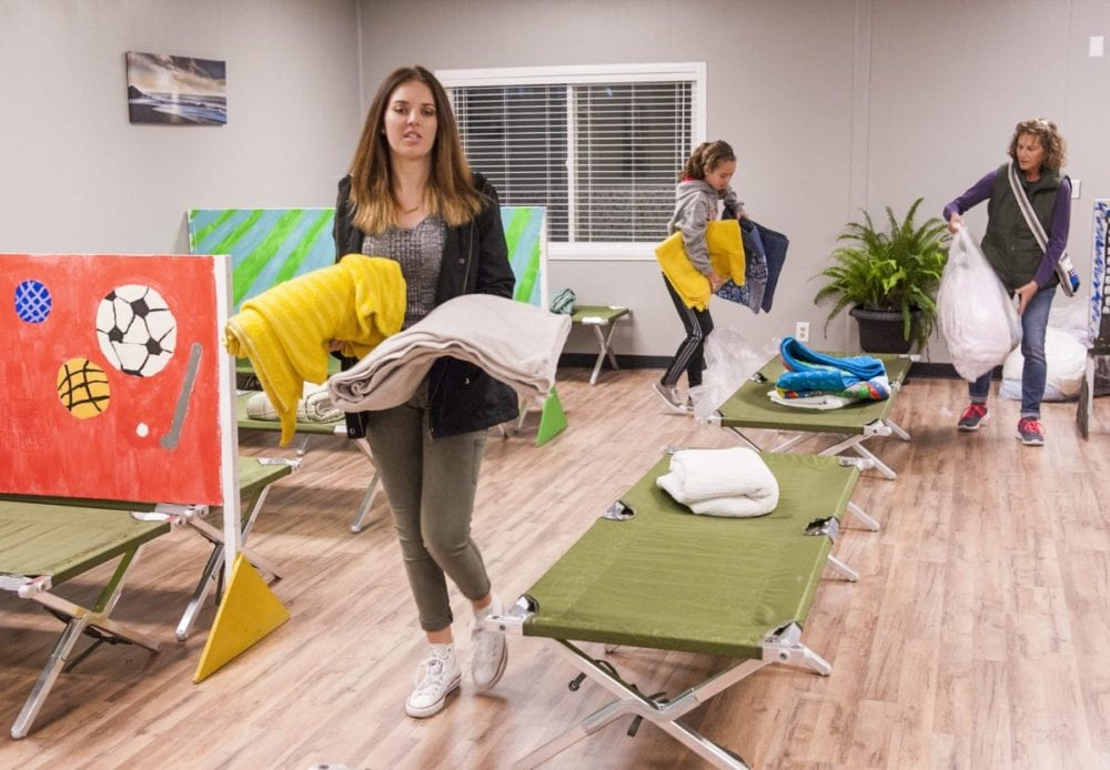 The Bridge to Home Shelter donations come from families, churches, scouts and businesses. Helping set up the sleeping quarters with blankets and towels are volunteers Haley (L) and Riley (C) Cabot and Resident Attendant Jayne Patafio (R). Photo Tom Cruze/For the Signal