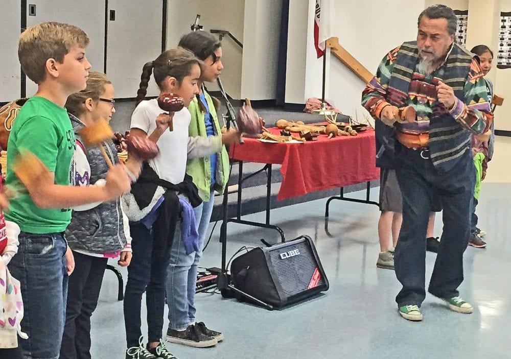 Northlake Hills Elementary School students in Kacy Duncan's, Meg Waymire's and Beth Chamberlin's fourth grade classes shake traditional rattlers and shakers as part of an interactive musical performance led by Native American musician Martin Espino during the school's first Native American Day. Christina Cox/The Signal