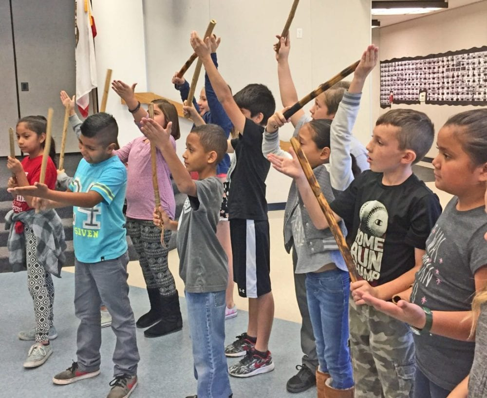 Northlake Hills Elementary School students in Kacy Duncan's, Meg Waymire's and Beth Chamberlin's fourth grade classes hold up traditional clapper sticks during the school's first Native American Day. Christina Cox/The Signal