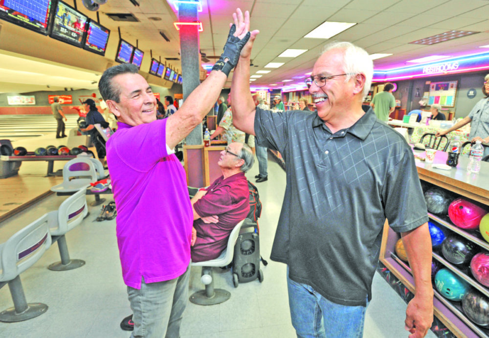 Senior bowlers Ed Limon, left, and Alex Hernandez hi-five after Limon got a strike at the 2016 North Los Angeles County United States Bowling Congress Senior Tournament held at Valencia Lanes in Newhall on Saturday. Dan Watson/The Signal