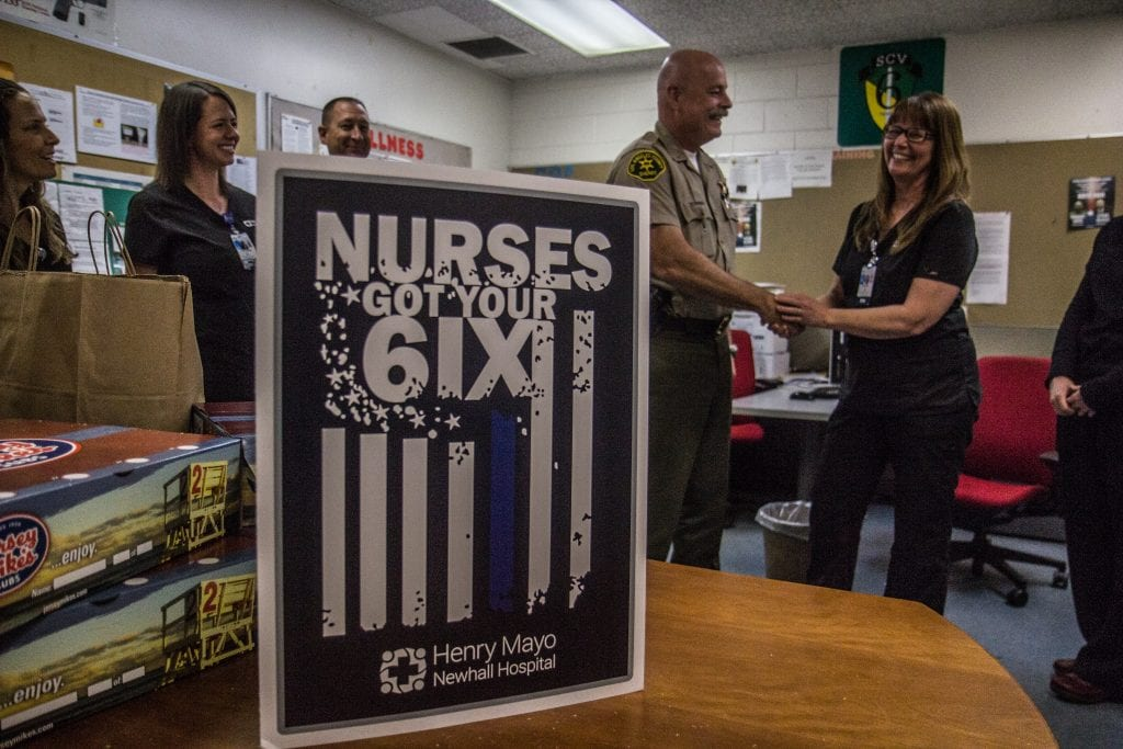 Sheriff's Lt. Rob Hahnlein shakes hands with a Henry Mayo Newhall Hospital nurse in the breakroom of the Santa Clarita Valley Sheriff's Station Monday. Austin Dave/The Signal