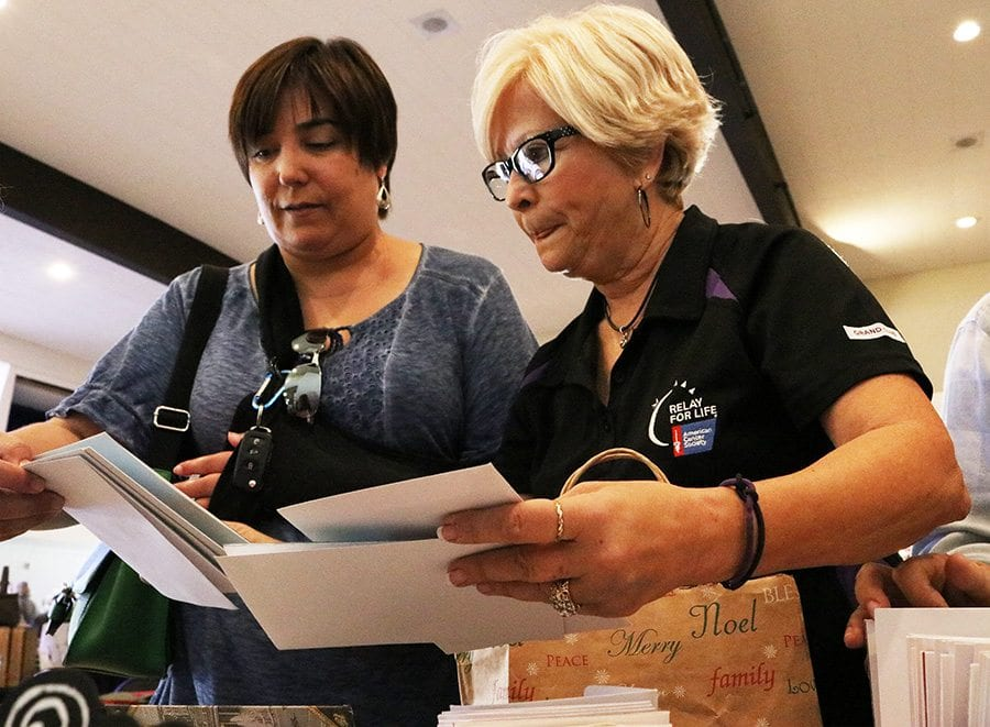 Kathleen Parvard, right, shows Jennifer Minard her home-made holiday cards at the eighth annual American Cancer Society 2016 Annual Relay for Life Holiday Boutique at Santa Clarita United Methodist Church on Saturday, Nov. 19, 2016. Nikolas Samuels/The Signal