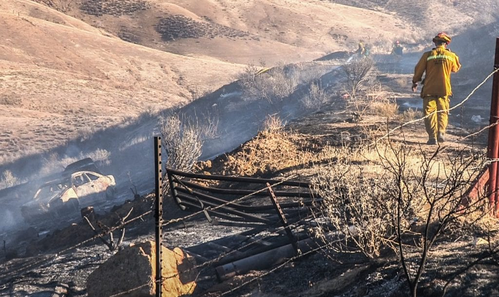 A Los Angeles County firefighter investigates a car wreck suspected of igniting a three-acre brush fire in Castaic Saturday afternoon. Austin Westfall/The Signal