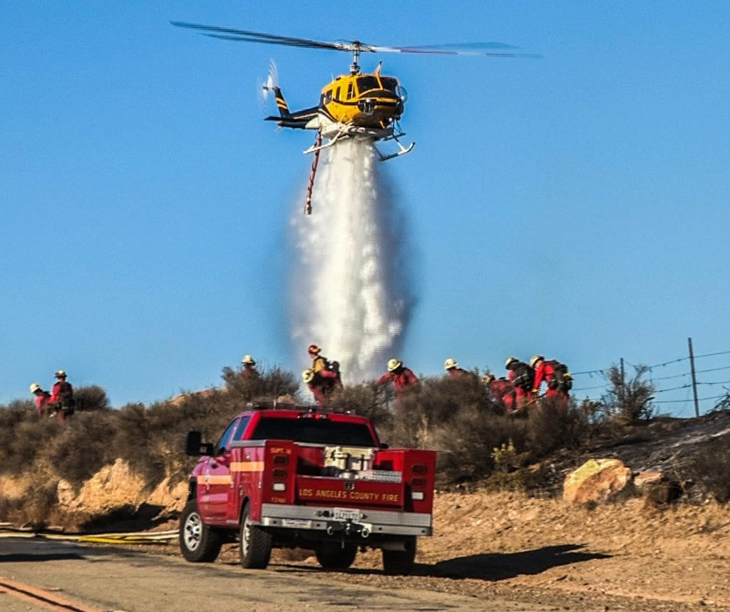 A helicopter drops water after a fire burned three acres of brush in Castaic Saturday afternoon. Austin Westfall/The Signal