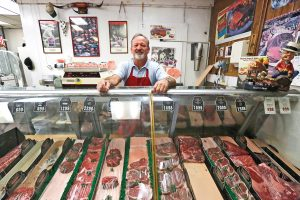 Keith Mowry, the owner of Bob's Country Meats, stands at the meat counter at the shop in Canyon Country. (Katharine Lotze / The Signal)