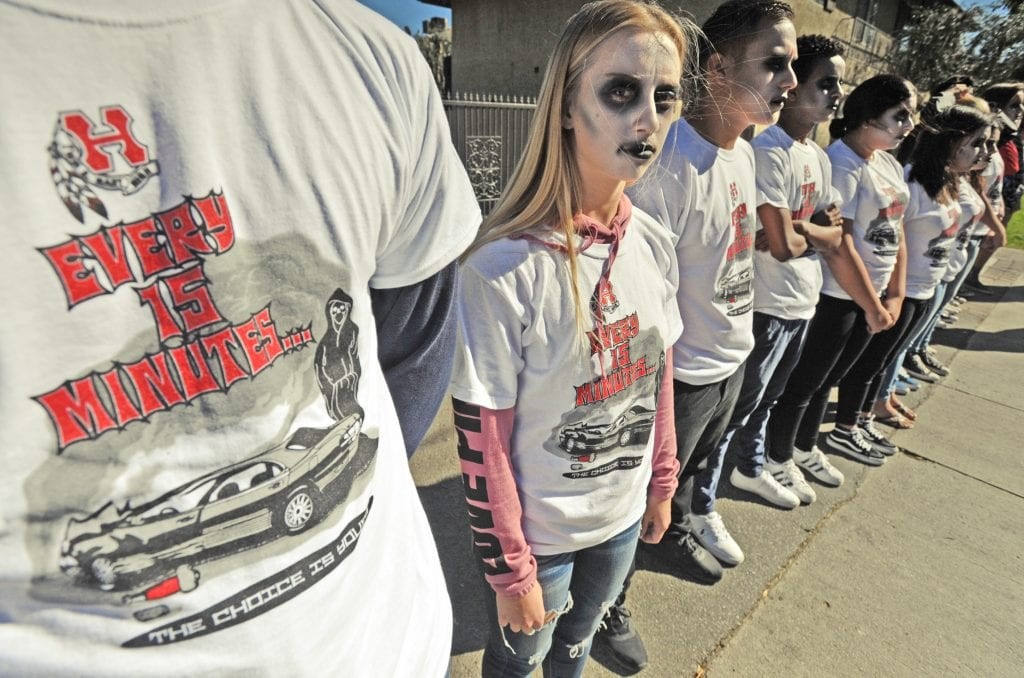 Hart High Student Maggie Doty, 17, center, stands with other Hart High students who represent the number of youngsters killed every 15 minutes in impaired driving incidents as they participate in the Every 15 Minutes presentation held in front of Hart High School in Newhall on Thursday. Dan Watson/The Signal